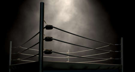 An old vintage boxing ring surrounded by ropes spotlit in the middle on an isolated dark background photo