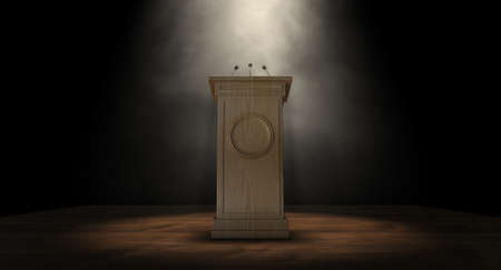 A wooden speech podium with three small microphones attached on a dark background spotlit by a single spotlight