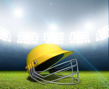 cricket helmet: A cricket stadium with a yellow cricket helmet on an unmarked green grass pitch at night under illuminated floodlights