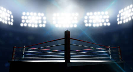 boxing match: An boxing ring surrounded by ropes spotlit by floodlights in an arena setting at night