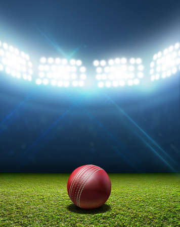 A cricket stadium with a red leather cricket ball on an unmarked green grass pitch at night under illuminated floodlights Stock Photo
