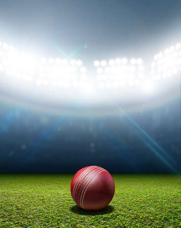 unmarked: A cricket stadium with a red leather cricket ball on an unmarked green grass pitch at night under illuminated floodlights Stock Photo
