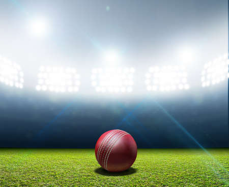 cricket: A cricket stadium with a red leather cricket ball on an unmarked green grass pitch at night under illuminated floodlights Stock Photo