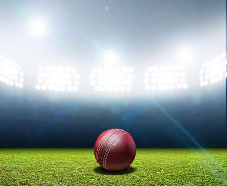 Een cricket stadion met een rood lederen cricket bal op een ongemarkeerde groene gras veld nacht onder verlichte schijnwerpers Stockfoto