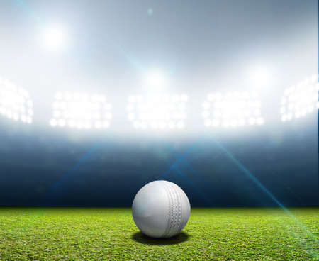 cricket ball: A cricket stadium with a white leather cricket ball on an unmarked green grass pitch at night under illuminated floodlights