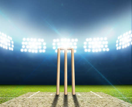 A cricket stadium with cricket pitch and set up wickets at night under illuminated floodlights