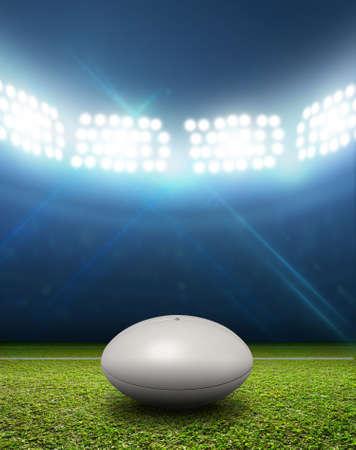 pelota de rugby: Un estadio de rugby con una pelota de rugby en blanco genérico en un marcado campo de césped verde en la noche con luz artificial iluminadas