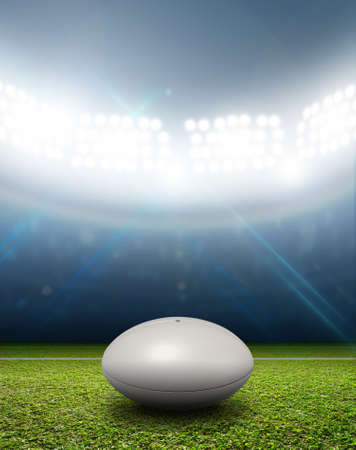 green grass: A rugby stadium with a generic white rugby ball on a marked green grass pitch at night under illuminated floodlights