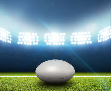 rugby field: A rugby stadium with a generic white rugby ball on a marked green grass pitch at night under illuminated floodlights