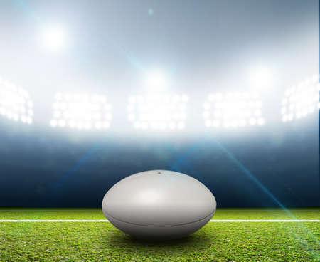 Ein Rugby-Stadion mit einem generischen weißen Rugbyball auf einem markierten grünen Rasenplatz in der Nacht unter Flutlicht ausgeleuchtet Lizenzfreie Bilder