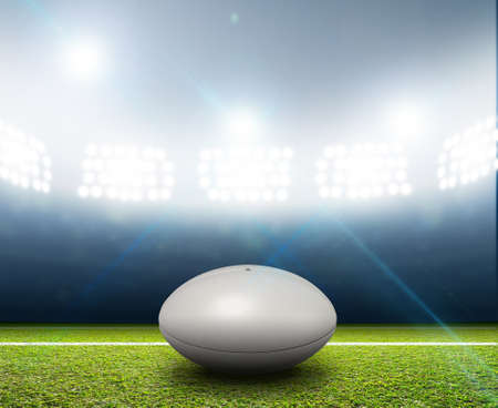A rugby stadium with a generic white rugby ball on a marked green grass pitch at night under illuminated floodlights