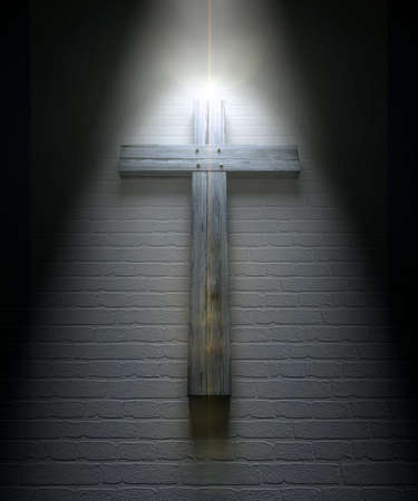 passion of the christ: A regular wooden crucifix mounted on a white wall under a spotlight Stock Photo