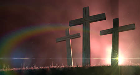 crucifixes: A concept of the crucifixion with three wooden crucifixes on a grassy hill backlit by an early morning sunrise