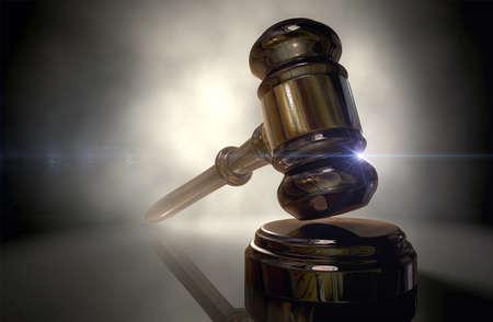 Een regelmatige houten veilingmeesters hamer of rechters hamer met koperen bekleding terug aangestoken op een donkere Stockfoto