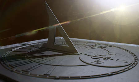 An extreme closeup of a section of an old vintage sundial clock made of scratched metal with roman numerals on a dark background