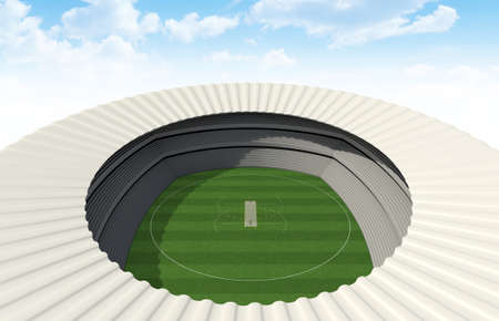 bails: A cricket stadium with a pitch on a marked green grass field in the daytime on a blue sky background Stock Photo