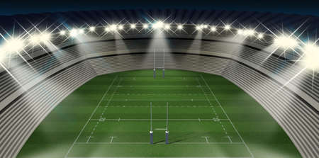 A rugby stadium with rugby posts on a marked green grass pitch in the night time illuminated by an array of spotlights