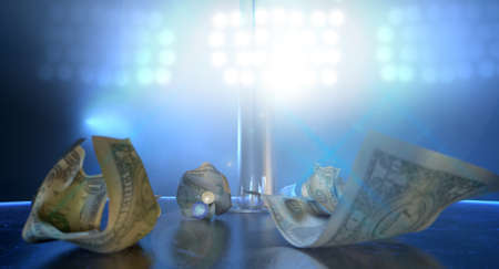 stripper pole: An isolated stripper pole on a stage lit by a single spotlight surrounded by crumpled up one dollar bill tips on a strip club  Stock Photo
