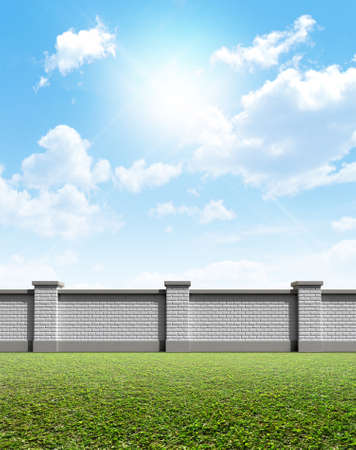 An front view of a regular domestic brick wall on a green grass and blue sky background photo