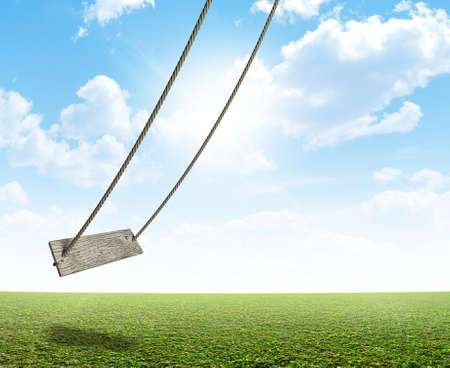 A regular home made swing made of rope and a wooden plank on a grassy field ground and blue cloudy sky background