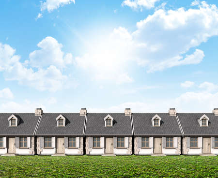 neighbours: A row of stone cottages with chimneys and shutters on a blue sky and grass lawn background Stock Photo