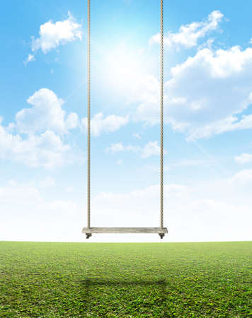 suspend: A regular home made swing made of rope and a wooden plank on a grassy field ground and blue cloudy sky background