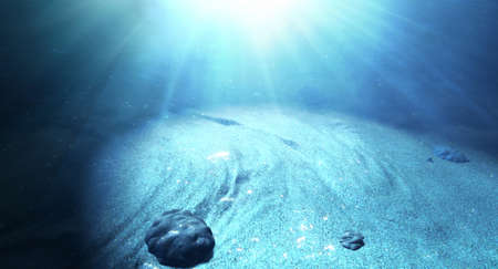 emanating: An underwater scene at the bottom of the ocean floor showing sand and emanating sunlight beaming through