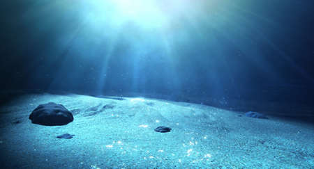 An underwater scene at the bottom of the ocean floor showing sand and emanating sunlight beaming through