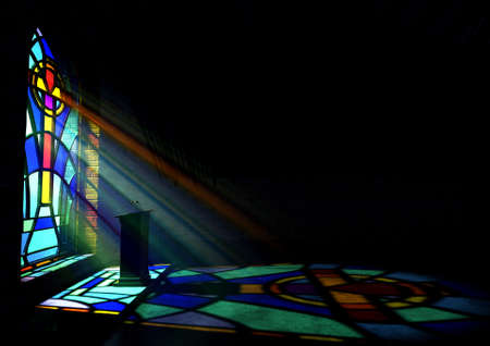 A dim old church interior lit by suns rays penetrating through a colorful stained glass window in the pattern of a crucifix reflecting colours on the floor and a speech pulpit Stockfoto