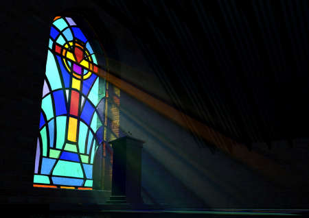 A dim old church interior lit by suns rays penetrating through a colorful stained glass window in the pattern of a crucifix reflecting colours on the floor and a speech pulpit Foto de archivo