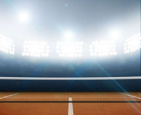 A tennis court in an arena with a marked orange clay surface at night under illuminated floodlights