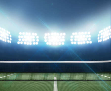 A tennis court in an arena with a marked green hard surface at night under illuminated floodlights