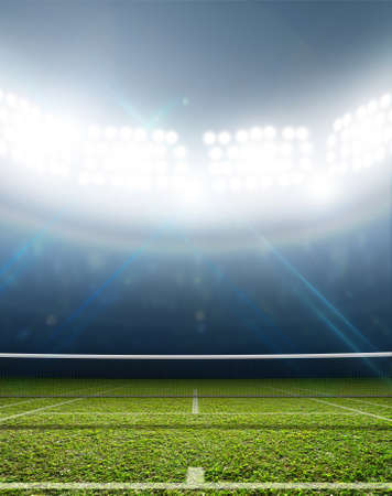 floodlit: A tennis court in an arena with a marked green lawn surface at night under illuminated floodlights Stock Photo