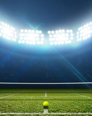 tennis net: A tennis court in an arena with a marked green lawn surface at night under illuminated floodlights Stock Photo