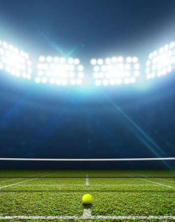 jugando tenis: Una pista de tenis en una arena con una superficie de césped verde marcada por la noche con luz artificial iluminadas Foto de archivo