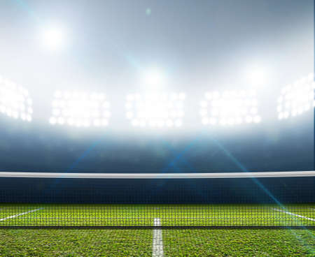 A tennis court in an arena with a marked green lawn surface at night under illuminated floodlights Stock Photo