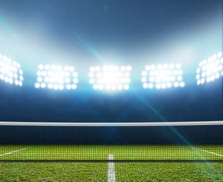 court: A tennis court in an arena with a marked green lawn surface at night under illuminated floodlights Stock Photo