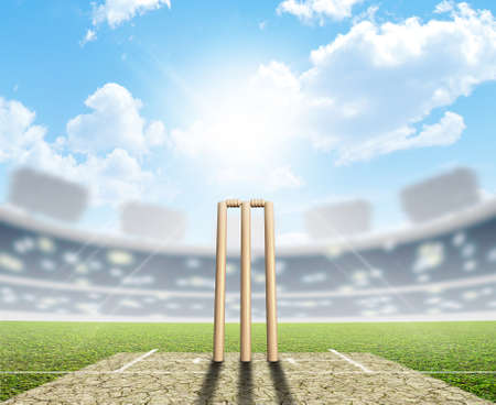cricket game: A cricket stadium with cricket pitch and set up wickets in the daytime under a blue sky Stock Photo