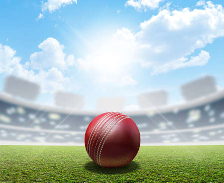 A cricket stadium with a red leather cricket ball on an unmarked green grass pitch in the daytime under a blue sky