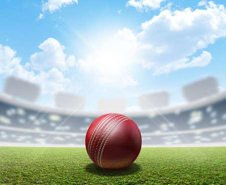 Ein Cricket-Stadion mit einem roten Leder Cricketball auf einem unmarkierten grünen Rasenplatz in der Tageszeit unter einem blauen Himmel