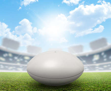 marked: A rugby stadium with a generic white rugby ball on a marked green grass pitch in the daytime under a blue sky Stock Photo