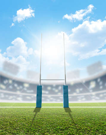 A rugby stadium with rugby posts on a marked green grass pitch in the daytime under a blue sky photo
