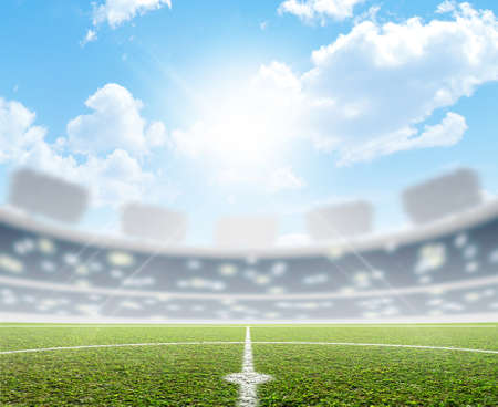 A soccer stadium with a marked green grass pitch in the daytime under a blue sky 스톡 콘텐츠