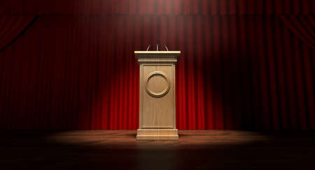 podium: A regular theater stage with closed red curtains and a wooden debate podium lit by a single spotlight Stock Photo