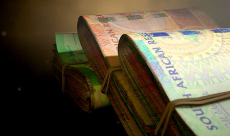 doubled: A close-up view of three wads of folded over stacks of south african banknotes each bound infomally by a rubber band on an isolated studio background Stock Photo