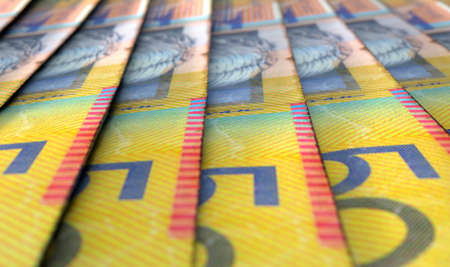 staggered: A macro close-up view showing the detail of australian dollar banknotes laid out and overlapping in a staggered row