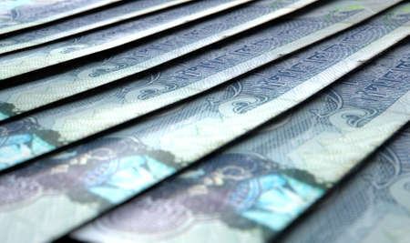 staggered: A macro close-up view showing the detail of dirham banknotes laid out and overlapping in a staggered row