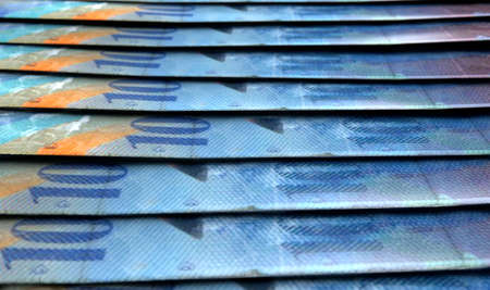 staggered: A macro close-up view showing the detail of swiss franc banknotes laid out and overlapping in a staggered row