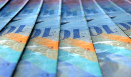 A macro close-up view showing the detail of swiss franc banknotes laid out and overlapping in a staggered row
