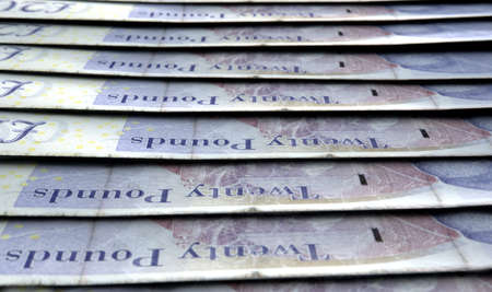 staggered: A macro close-up view showing the detail of british pound banknotes laid out and overlapping in a staggered row Stock Photo